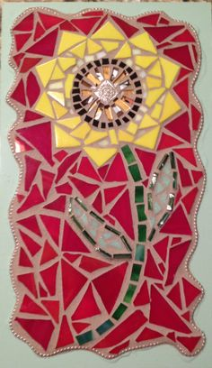 mosaic sunflower on repurposed wood flooring. made from stained glass, ball chain, and glass tiles.