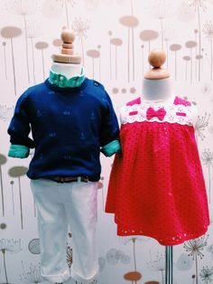 2014 Spring/Summer Apparel Collection. Left mannequin: Mayoral green button-up shirt paired with Mayoral navy sweater with fish and anchor detail and Mayoral white chino pant. Right mannequin: Mayoral red eyelet dress with white eyelet and bow detail.