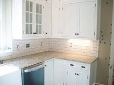 white kitchen subway tile with white cabinets and beige/brown countertop
