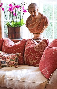 Family-Friendly English Country House A stately stone bust overlooks pillows from Andrew Martin in the crimson library - Traditional Home - Library Details