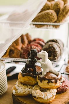 Dinosaur cake toppers, ok doughnuts toppers, same thing! | Super fun & wonderfully whimsical eclectic wedding at Griffis Sculpture Park inspired by the colors of BMW's M series | Photograph by Carolyn Scott Photography  http://www.storyboardwedding.com/eclectic-picnic-griffis-sculpture-park-offbeat-wedding-among-the-art/