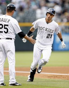 Colorado Rockies' Tyler Colvin (21) is greeted by third base coach Rich Dauer as he rounds third base after hitting a solo home run off Oakland Athletics starting pitcher Bartolo Colon during the first inning of an interleague baseball game, Tuesday, June 12, 2012, in Denver. (AP Photo/Jack Dempsey)