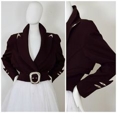 Features - 100% Authentic THIERRY MUGLER. - Dark brown cinch belted crop jacket. - Futuristic cut with metal embellishments on the cuffs and collar. - Massive belt buckle. - Silver tone hardware. - Fully lined and padded shoulders. - Label reads: THIERRY MUGLER PARIS Made in France, Size 40. - Excellent vintage condition.  Measurements taken laid flat: Shoulder: 19 4/8 inches (49.53 cm) Sleeves: 22 inches (55.88 cm) Bust: 39 inches (99.06 cm) Waist: 30 inches (76.2 cm) Length: 19 6/...