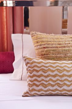 Details Photo - Textured pillows arranged atop white bed linens