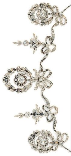 A Belle Epoque Diamond Necklace. The diamond-set ribbon bow front suspending three graduated diamond-set foliate wreaths with diamond cluster centre with two foliate spray pendants between, in millegrain settings, to a fine trace-link chain, circa 1910. #BelleÉpoque #necklace