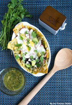 A recipe for chilaquiles made with tomatillo salsa, also known as green salsa. This vegetarian recipe includes black beans, avocado and egg.