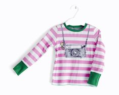 Super quirky instamatic camera fan t-shirt. It features an original illustration by artist Elisabetta Stoinich from MrsPeggottyArts for bymamma190 (Look at her work herehttps://www.etsy.com/shop/MrsPeggottyArts)  Girls t-shirt, long sleeve, bright green ribbing accents. This is a great piece to have for everyday wear. 100% cotton interlock. This whole garments are made in Italy. Meticulous attention to detail in order to make kids feel always comfortable. Perfectly sewn. All seams are…