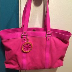 "Tory Burch Jane Tote Size: 16.5X11.5Tory Burch Tory Burch ""Jane"" tote bag.  Large pink canvas bag has patent leather handle, trim, and bottom with gold feet. A large hanging gold logo medallion hangs from strap. Taupe interior with pink patent trim. All hardware is embossed with Tory Burch. Interior has one zippered pocket and two slot pockets for cell phone, lipstick, etc. There is a white scrape on the strap.  Excellent condition-barely used, comes from smoke-free home. Tory Burch Bags…"