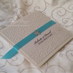 Pebble pocketfold wedding invitation with aqua ribbon and starfish as a beach themed accent by Wedding Invitations by Tango Design