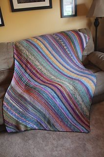 "This is a very scrappy sock yarn blanket with very little rules. Use as many or as little different colors as you like. A true stash buster! You could easily use any weight yarn and size needles to use up your stash. When knitting in sock weight and it measures 48"" x 72"", there are approx 240,600 stitches!!! There is not a purl stitch in sight! Just garter, nothing but potato chip knitting."