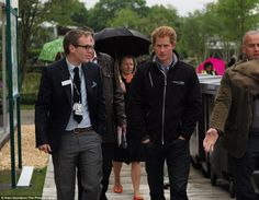 The brollies are out, it must be summer in England! Prince Harry braves the rain to get a first glimpse at the garden he created this year