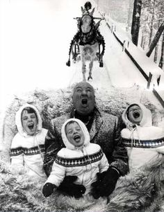Alfred Hitchcock, the family man, catching snowflakes during a sleigh ride with his grandchildren, 1960