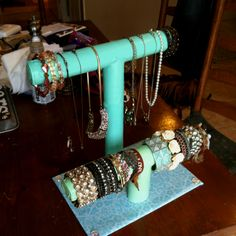 My very easy DIY jewelry holder - All it takes is paper towel rolls, a wooden base, scissors, and lots of hot glue. So cute for dorm rooms.