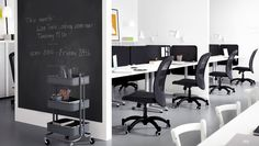 Office hotel furnished with black office chairs and black screens between white desks