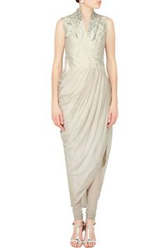 Gaurav Gupta Indian Designer Silver Fern Draped Kurta Set Featuring a mist grey draped kurta set with V neckline and copper fern zari embroidered bodice . It has a concealed side zip closure. It comes along with matching churidar and dupatta. Shop now-www.carmaonlineshop.com #carma #carmaonline #fashion #indiandesigner #GAURAVGUPTA #grey #kurtaset #classy #elegant #shopnow #onlineshopping