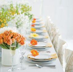 Fleurs oranges pour la table de mariage de printemps. N'oubliez pas la décoration des assiettes