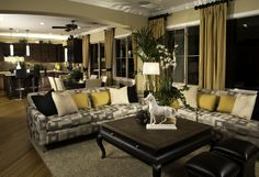 Subtle black, white, and gold theme runs throughout this immense open living room space, from drapes down to the twin leather ottomans. Patterned sectional wraps around large carved wood coffee table, while dining and kitchen spaces share the opposite end of the room.
