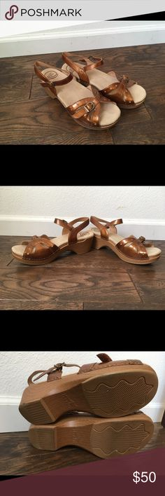 Dansko bronze leather sandal clogs size 40 From Dansko, shiny bronze leather sandals, with a clog base. In great condition. Only worn once. Super soft, cushioned footbed, with no foot indentations. No wear on buckles or elastic. They are a little dusty from sitting in my closet. Dansko Shoes Mules & Clogs