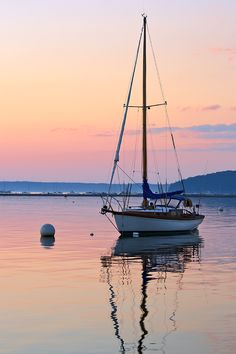 """An anchored sailboat and sunrise reflected in the calm waters of Frenchman Bay, Bar Harbor, Mt. Desert Island, Maine."""