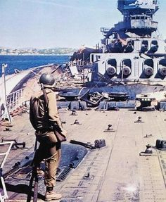 American soldier on the deck of the destroyed French battleship Strasbourg in Toulon,august 1944. Near the battleship on its side is the light cruiser La Gallissoniere.