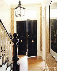 love the drama - the black and white staircase with the warm gold wallpaper. Love the lantern too. The black doors are very sophisticated.