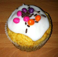 Cupcake de chocolate blanco con cobertura de glacé y topping de fideos de chocolate y lacasitos