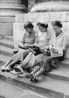 Leserinnen in London, 1937 Timeline Classics/Timeline Images #Mode #30er #30ies #Damenmode #Kleid #fashion #jung #Frauen #Mädchen #lesen #Zeitschriften #Treppenstufen #sitzen #historisch #schwarzweiß #schwarzweiss #Freundinnen #Mode #Mittagspause #Freizeit #lifestyle