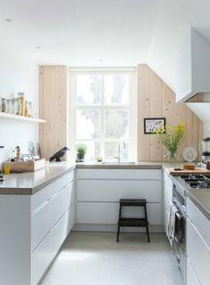 une jolie cuisine sous pente avec plafond blanc et meubles blancs