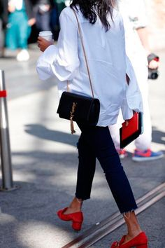 Street style de camisa branca oversized, calça skinny cropped, sapatos vermelhos e bolsa de alça de corrente