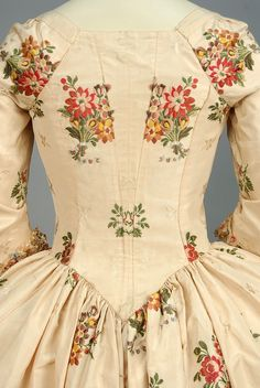 SILK BROCADE ROBE a L'ANGLAISE, CANADIAN, 1750 - 1775. Ivory silk brocaded with small tone on tone flowers and larger polychrome floral clusters, semi boned bodice with square-cut neckline and elbow length sleeve, pleated cuff decorated with fancy cord and polychrome tassels, trained open skirt with cord-trimmed furbelows, matching petticoat, bodice lined in cotton and linen.