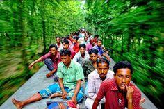 Bravant le danger, perchés sur les wagons d'un train en marche, des voyageurs aux faibles moyens se déplacent comme ils peuvent à travers le Bangladesh. Reportage avec Gmb Akash.