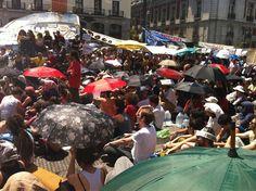 """Fecha: 22/5/11. Hora: 13.35. Tuit original: """"Los paraguas, la crema solar y el agua proliferan por la asamblea para combatir el calor sofocante. #acampadaSol""""."""
