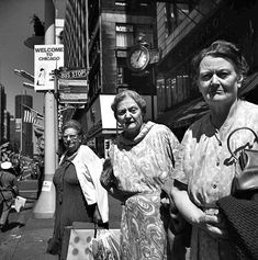 Three older women in dresses standing side by side at a bus stop while looking at the camera and a city street scene behind them. See a Stunning New Set of Vivian Maier Photos from Eye to Eye | Chicago magazine | July 2014