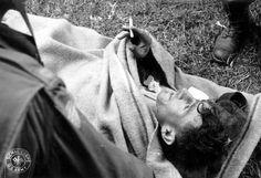 Un blessé allemand allongé sous une couverture dans une civière fume une cigarette. Au premier plan l'épaule droite d'un para de la 82nd US AB avec le drapeau américain, en arrière plan les bottes de saut d'un para US. Poste de secours de la 307th Airborne Medical Company de la 82nd US AB installé dans une ferme près de Sainte-Mère-Eglise.