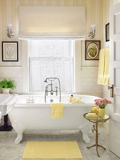 A claw foot tub and vintage-style fixtures by Porcher reinforce the traditional look of this master bath.