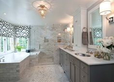 Glam gray master bathroom with charcoal gray double bathroom vanity, paired with white quartz countertop and hammered metal his and her sinks. Seamless glass shower with marble tile shower surround and rain shower head. Gray bathroom walls paint color, custom roman shades in F Schumacher Zimba Charcoal Fabric and drop-in tub with marble surround.
