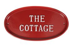 Solid cast oval house sign with The Cottage in raised hand painted text.