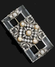 A DIAMOND NATURAL PEARL ROCK CRYSTAL PLATINUM AND 18K WHITE GOLD BROOCH CIRCA 1925.