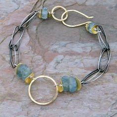 Handmade bracelet.  Hand oxidized silver links, grade A aquamarine, handmade gold circle ad handmade gold clasp.