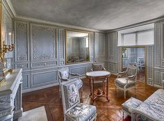 SALON LOUIS XVI LE PETIT TRIANON VERSAILLES FRANCE The furniture, fabric, wood paneling, and color scheme of the room is typical of the period.