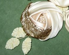 Cabochon rose is hand sewn with silk bridal satin with an overlay of antique gold metal lace. Rose has a center bud of freshwater pearls and vintage ribbon leaves on silk covered wire stems. Color of rosette is a creamy ecru. Size is 3 by 6 inches and about 2 inches high