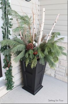 See how I made these gorgeous urns with curb appeal! Decorating tips for your winter porch - birch branches, curly willow, large pine cones and fresh greenery.