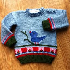 Knitting Pattern for Songbird Sweater - This pullover features a colorful intarsia bird and flower pattern and buttons at one shoulder for easy dressing. Sizes 6-18 months. One of the patterns in 60 Quick Baby Knits. Pictured project by PDamon