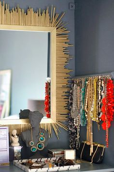 dominoCREATE A VANITY AREA FOR JEWELRY STORAGE.  To keep my accessories organized, I created a vanity by installing one of the IKEA shelves at counter height above a series of drawers used for clothing storage and adhering a mirror to the back of the wardrobe. Then, I affixed 40 small brass hooks to a scrap piece of wood and hung it inside for necklace storage.