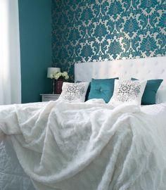 Rohkea turkoosi tapetti ja koristetyynyt tuovat ylellisen pirteän värin makuuhuoneeseen.