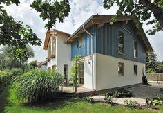 Das großzügige Haus im Landhausstil lebt von dem Kontrast zwischen weißem Putz und taubenblauer Holzschalung, der Sommerfrische und Kaminwärme gleichermaßen vermittelt. Trotz der traditionellen Elemente ist die Formensprache klar. Das helle Holz als Akzent rundet den Gesamteindruck ab. Die großzügige Holzterrasse lädt zum Verweilen ein. 189 m² Gesamtwohnfläche