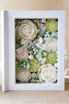 ウェディング&出産祝&母の日の記念にソーラーローズとアーティフィシャルフラワーを詰め込んだフォトボックスをプレゼントしてみませんか?花材は白とグリーンのソーラーローズを埋め込んで、その周りにアーティフィシャルフラワー、色とりどりのパールピック、メッセージを印刷したサテンのリボンをアクセントに飾りました。とてもエレガントなので、お部屋のインテリアには勿論、 お友達へのギフト、ウェディングのギフトにもぴったりです。 入学の記念のギフトとして喜ばれそうですね(#^.^#) ※4枚目の画像のフレームにお好きな写真やカードを入れてください。フォトフレーム部とアレンジルーム部はマグネットで吸着するので、余計な金具が見えたりしないすっきりとした形になっています。今回はリボンをウェディングのメッセージにしましたがこちらはお好みのメッセージを印刷できますのでお祝いのシチュエーションに合わせてお作りします。尚、ギフトラッピングご希望の方はこちらもカートに入れてください。 http://www.creema.jp/exhibits/show/id&#x...