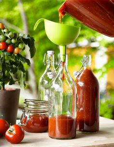 Domácí kečup je pomocí trychtýře naléván do skleněné láhve.