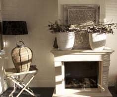 Schouw van natuursteen met een gashaard, zandstenen potten gedecoreerd met takken.