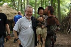 "Russell Crowe kissing an extra on the set of the 2010 film ""Robin Hood"" with director Ridley Scott."